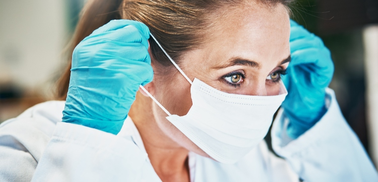 A blonde woman wearing a lab coat and surgical gloves puts on a surgical mask.