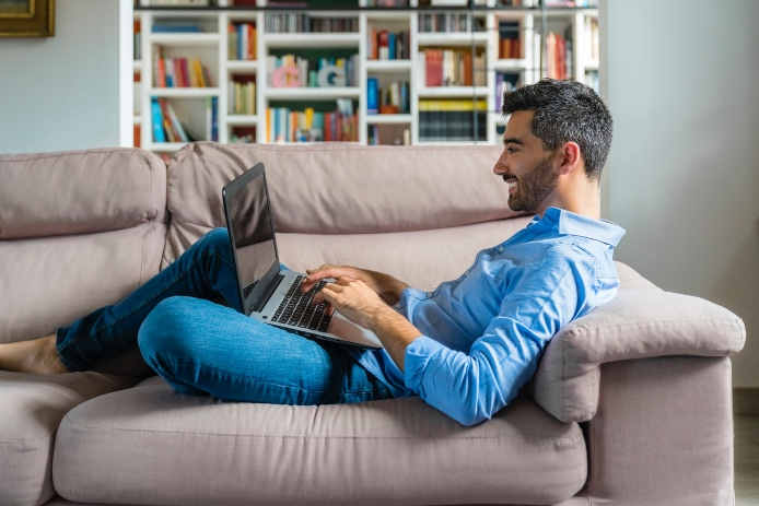 Smiling young man lying on the couch at home using laptop