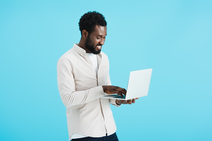 smiling african american man in white shirt using laptop isolated on blue
