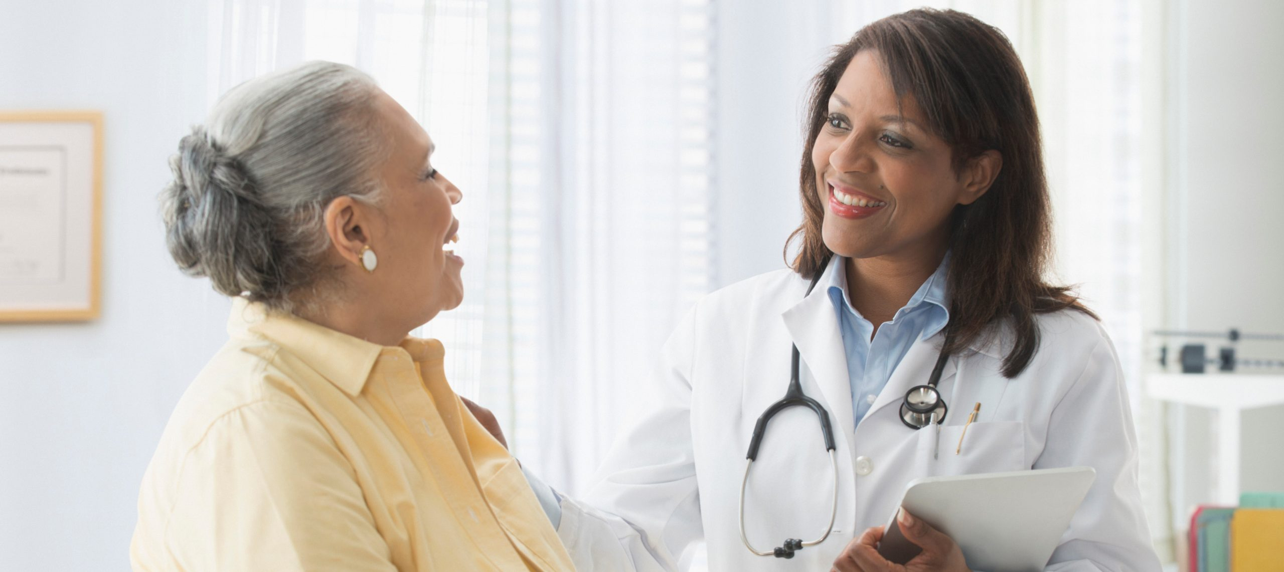 Older woman talking to doctor in office